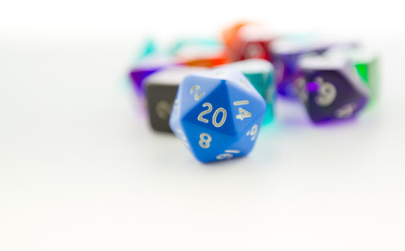 heap of role: Macro shot of twenty sided dice with other dice out of focus on a white background Stock Photo