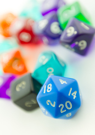heap of role: Tilted macro shot of blue twenty sided dice with other dice out of focus on a white background