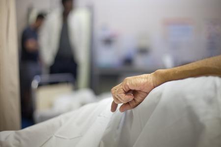 病院のベッドで彼の側で老人の手がかかっています。 写真素材