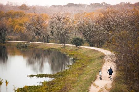 ヒューストンの近くの国立公園の父と息子の自転車 写真素材