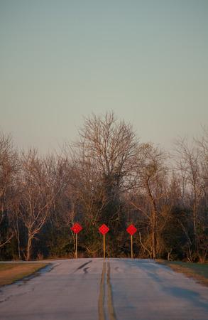 冬に道路の端に 3 つの赤い行き止まり標識