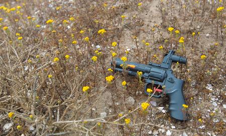 黄色い花を持つ汚れで黒いおもちゃ銃