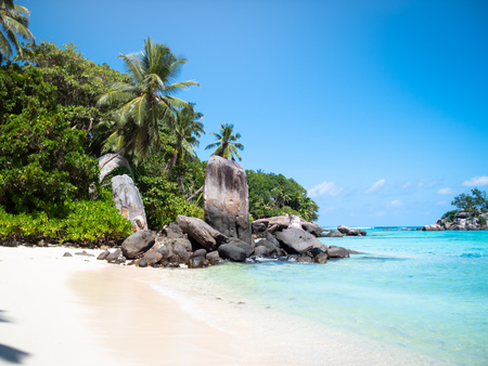 Seychelles beach with exposed rocks and distant island