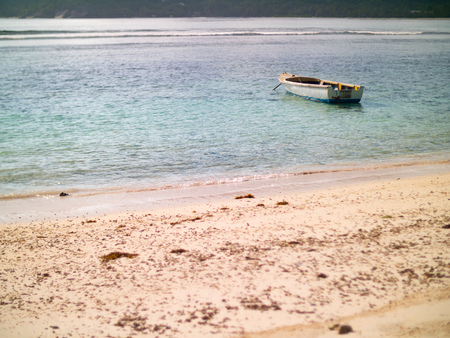 Small boat anchored off a Seychelles beach 写真素材