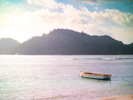 Small boat anchored off a Seychelles beach with light leak 写真素材
