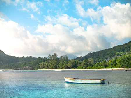 Small colorful boat anchored off a Seychelles beach with distant shore 写真素材