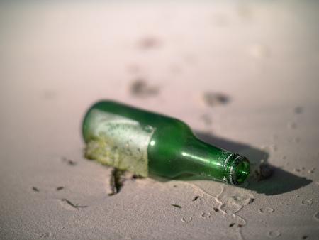 Green bottle lying on a Seychelles beach 写真素材