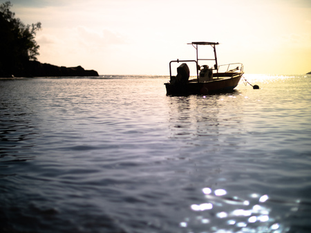 Low angle of a small anchored motor boat silhouetted during a Seychelles sunset 写真素材