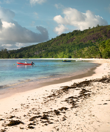 Red motor boat anchored off a sunny Seychelles beach with distant clouds