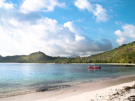 Red motor boat anchored off a sunny Seychelles beach with distant clouds and shoreline