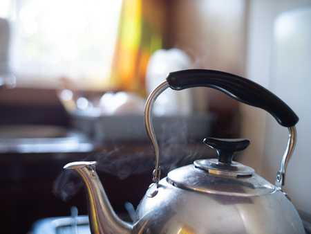 Silver reflective kettle with black handle steaming
