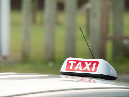 Taxi sign and aerial mounted ontop of a car with a reflection in the Seychelles