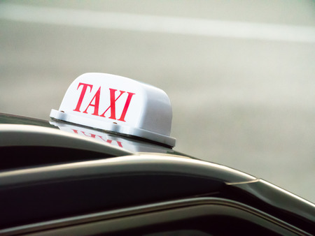 Taxi sign mounted ontop of a black car with a reflection in the Seychelles