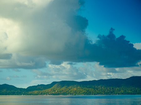 Large cloud formations over the ocean with distant green hills in the Seychelles 写真素材