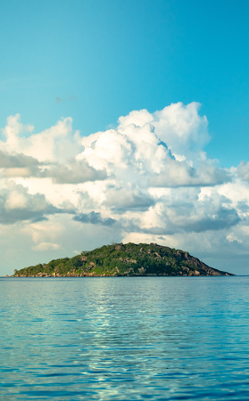 Low angle of a rocky green island with large cloud formations in the distance in the Seychelles