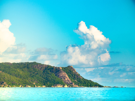 Blue waters of the Seychelles with green rocky outcropping and cloudy skies 写真素材