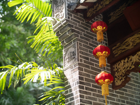 Chinese paper lanterns on a grey brick archway with engraved wood in the Seychelles Stock Photo