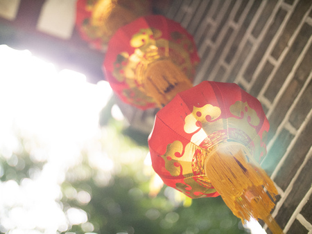 Chinese paper lanterns with light bleed on a grey brick archway with engraved wood in the Seychelles