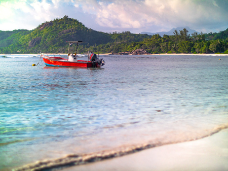 Small red motorboat anchored off a Seychelles beach on a sunny yet overcast day. Green hills in background framing a strip of beach.