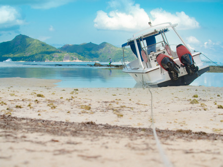 Motorboat moored off a Seychelles beach. Still waters under cloudy sky with jungle covered hills in the background.