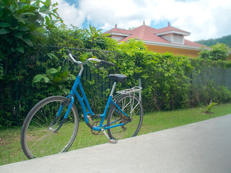Blue bicycle left standing along a road in a suburb of Victoria in the Seychelles. 写真素材