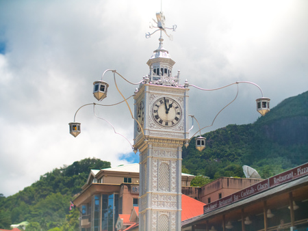 Victoria Clock Tower in Victoria, Seychelles. Bright but cloudy day with green jungle covered hills in background.