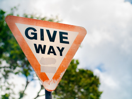 Give way sign on a suburban road under overcast skies in the Seychelles.
