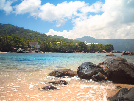 Water lapping against rocks on a Seychelles beach during a sunny day with large clouds.