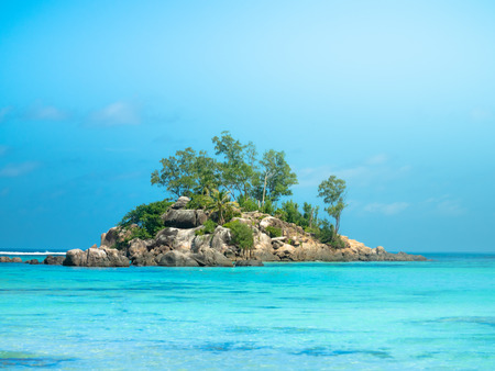 Small rocky island off the coast of the Seychelles with beautiful blue waters and sunhine.