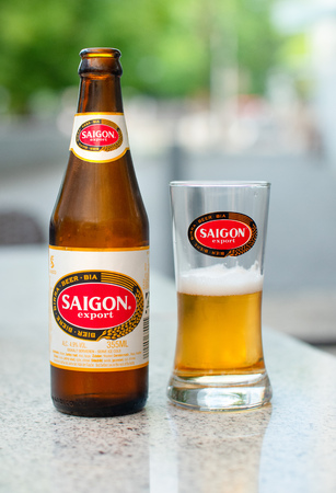A Saigon beer bottle and glass on a marble table at a street cafe