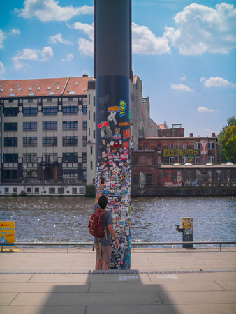 Tourist takes a photo of a sticker covered pole by a river in Berlin