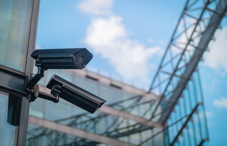 Pair of surveillance cameras on the side of a modern building 写真素材