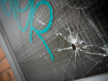 Bullet hole and cracks in a reinforced window with gang graffiti