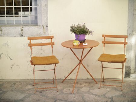 Orange metal chairs and table on the street in Greece