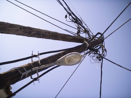 Loads of Powerlines and streetlamp on wooden poles