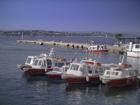 Multiple red and white boat taxies at a pier in Greece