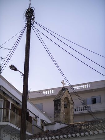 powerlines above an old church steeple in Greece