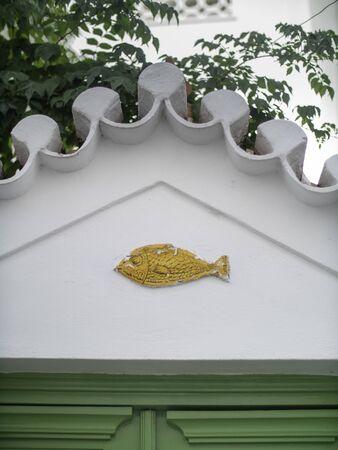 Yellow fish carving above a green door Standard-Bild