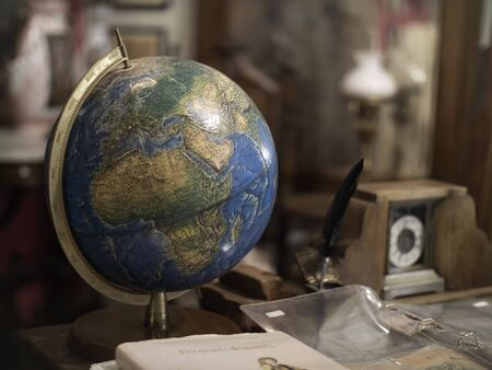 An antique globe on a desk with other old objects