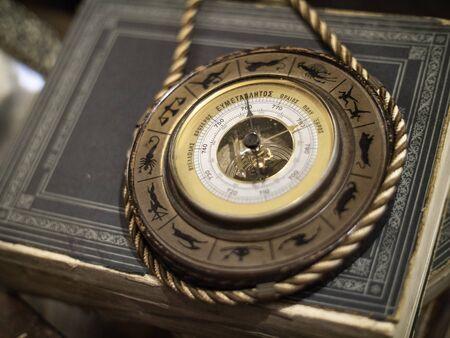 an antique barometer wth zodiac symbols on a book
