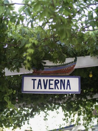 A blue and white tavern sign surrounded by vines in Greece