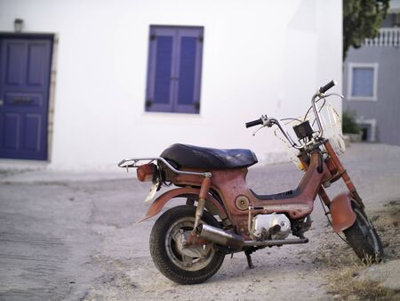 an old rusted red scooter in Greece with blue door and window