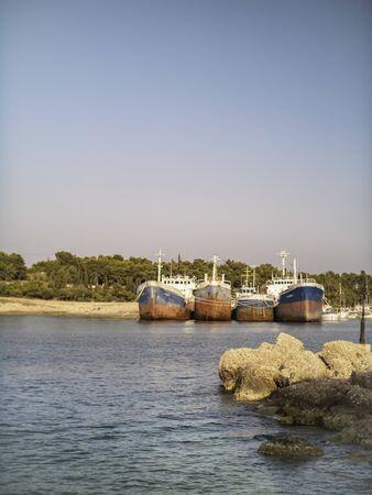 Big fishing boats moored together on a Greek isle