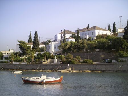 Smail boat anchored below island houses on Spetses