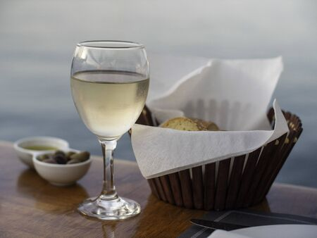 A glass of white wine with bread by the water Standard-Bild