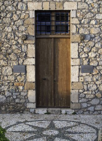 heavy wooden door in stone wall with compass in the tiles