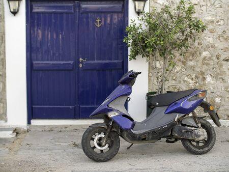 blue scooter by a blue door in Greece Standard-Bild