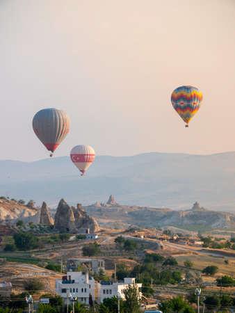 Hot air balloon tours flying over the town of Göreme in Cappadocia Editorial