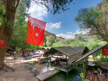 restaurant over a river in cappadocia flying turkish flags