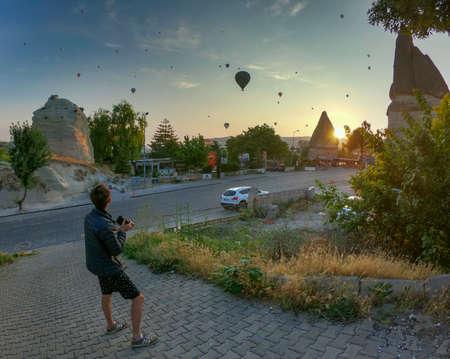 a man photographs hot air balloons over Goreme in cappadocia